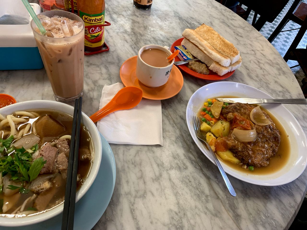 Breakfast with beef noodle soup, milk tea and toast with coconut paste